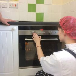 young person setting timer on cooker