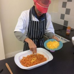 young chef adding cheese to pasta and sauce