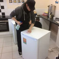 Young person cleaning the top of the fridge